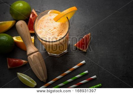 Citrus drink. Fresh citrus smoothie juice at dark background. Top view with copy space