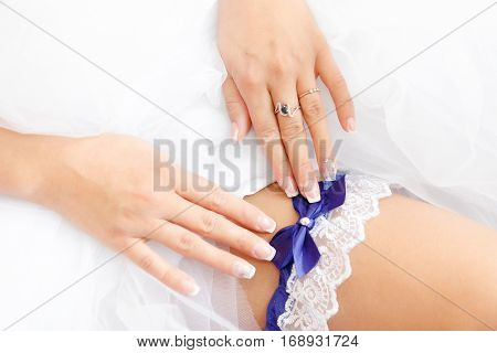 bride is wearing a beautiful garter before the wedding