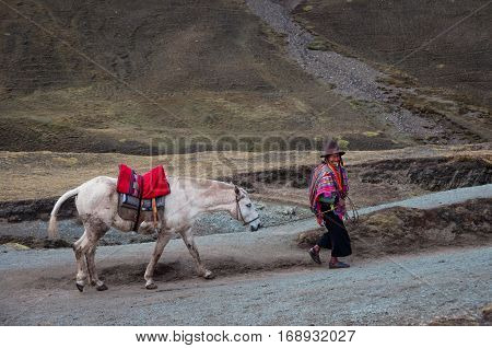 RAINBOW MOUNTAINES PERU - OCTOBER 8 2016: Native peruvian man wearing traditional clothes and hat with his horse goes uphill.
