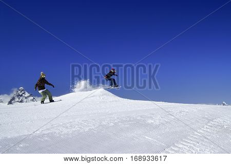 Two Snowboarders Jump In Snow Park At Ski Resort On Sunny Winter Day