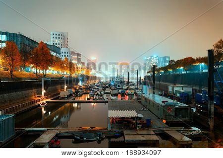 Golden autumn in Dusseldorf city. View on harbor with a lot of boats and excessive light on background from illuminated buildings.