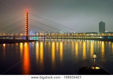 Bridge over the Rhine river in Dusseldorf city at night with colorful illumination reflected in water. Lonely lantern at the bank of the river.