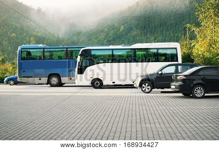 Cars and buses in a parking lot on mountains background