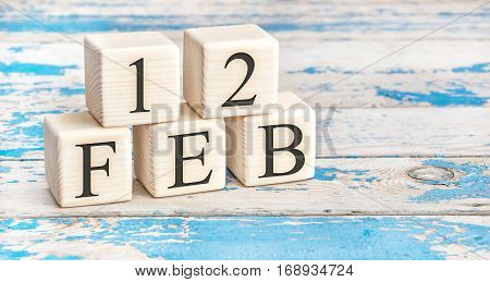 February 12th. Wooden cubes with date of 12 February on old blue wooden background.