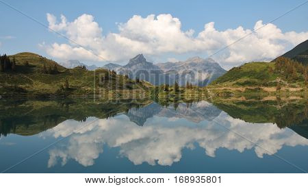 Summer clouds and mountains mirroring in lake Trubsee Engelberg. Landscape halfway up on mount Titlis Switzerland.