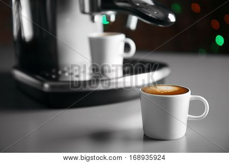 Cup of fresh espresso with coffee maker on grey table