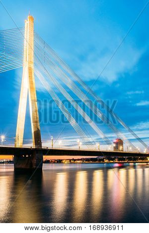 Riga, Latvia. Scenic View Of  Vansu Cable-Stayed Bridge In Bright Night Illumination Over The Daugava River, Western Dvina And Color Reflexions On Water Surface.