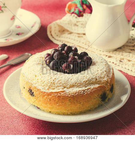 Blackcurrant cake on pink background with tea, square, toned