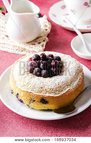 Blackcurrant cake on pink background with tea, vertical