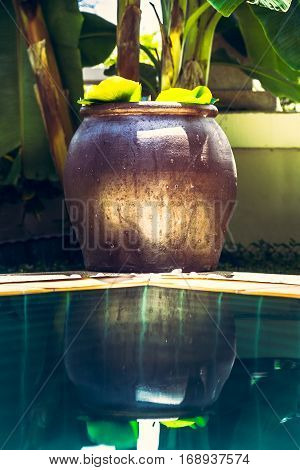 Asian Zen style decoration bowl at pool with turquoise water and reflections in tropical garden with lush tropical foliage