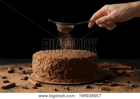 Woman powdering chocolate cake with cocoa powder