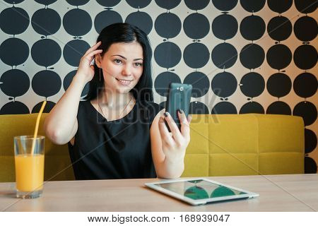 Young attractive model girl aged 20s making selfie photo using a smartphone indoors