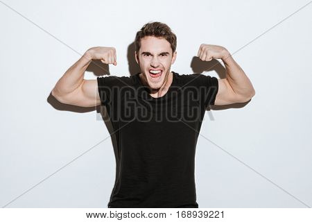 Picture of screaming young man dressed in black t-shirt posing over white background looking at camera. Showing biceps.