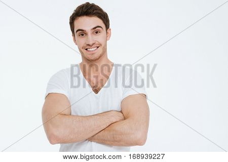 Picture of young cheerful man dressed in white t-shirt standing over white background with arms crossed