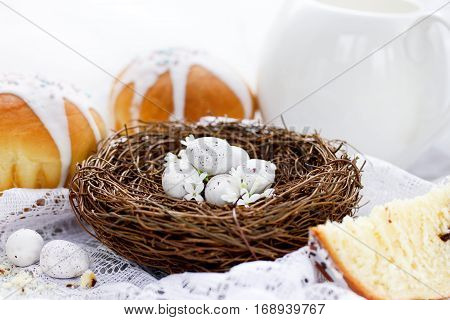 Easter bird nest with white speckled eggs and Easter cake on the table - Easter decorations and traditional treats beautiful Easter composition