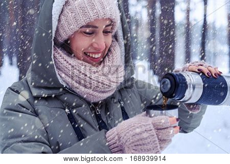 Side view shot of smiling young woman with cup in winter forest. Model pouring hot tea from the thermos in snowy forest