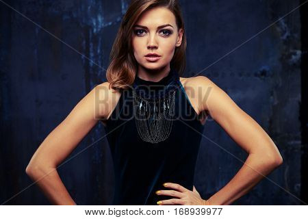 Mid shot portrait of stunning beauty of gorgeous woman wearing vinous evening dress posing at the camera over black background