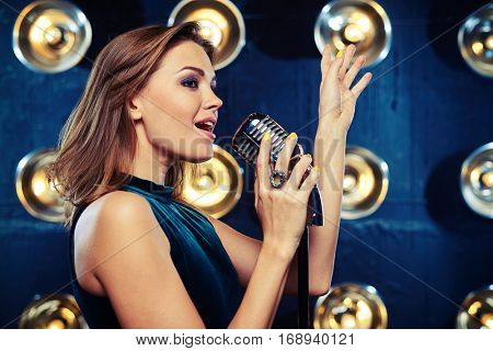 Side view mid shot of stunning female vocalist singing with feelings and raising hand up. Brown haired girl with straight hair. Beautiful girl with shoulder-length straight hair. Perfect makeup