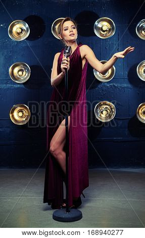 Mid shot of well-dressed young female vocalist in shiny black evening dress singing with emotions in front of standing silver microphone