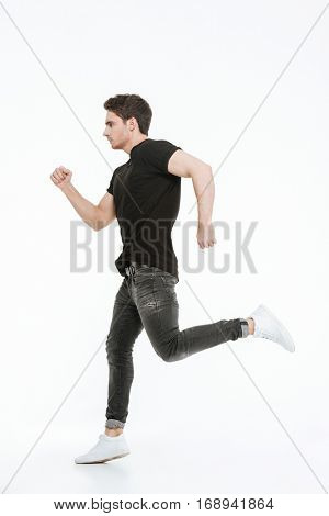 Image of handsome young man dressed in black t-shirt running over white background looking aside.