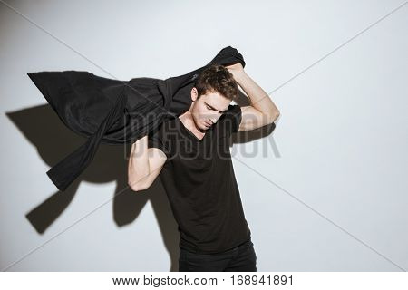 Image of young handsome man dressed in black t-shirt and mantle standing over white background and posing.
