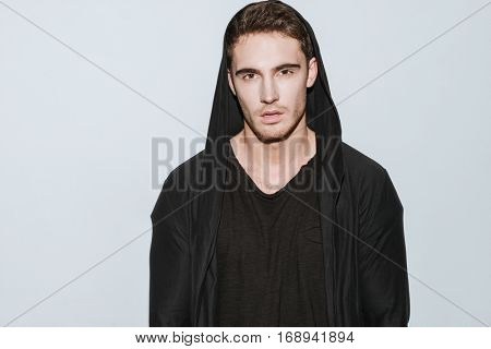 Image of young attractive man dressed in black t-shirt and mantle standing over white background.