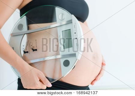Weight gain during pregnancy with pregnant woman holding scale poster