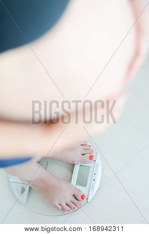 Pregnant woman weighing herself on a bathroom scale