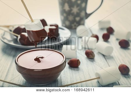 Chocolate fondue with marshmallow on table