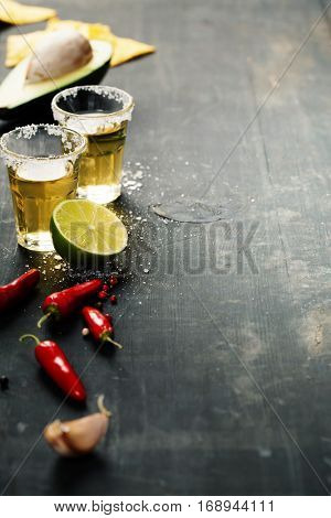 Tequila shots and mexican ingredients on rustic table