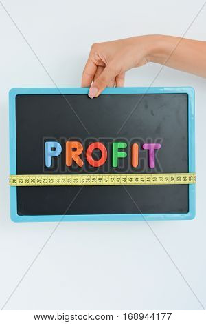 Measure your profit concept written as magnetic colored letter blocks with scale
