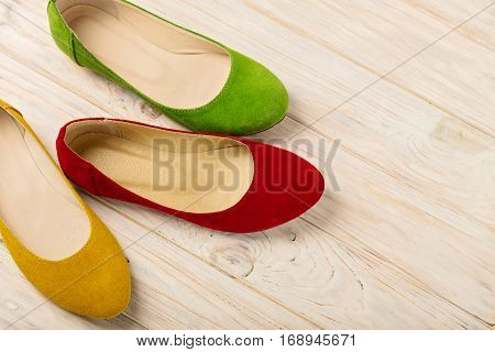 Red green and yellow women's shoes (ballerinas) on wooden background. Selective focus.