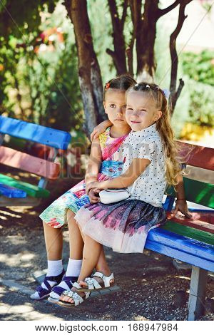 two happy little fashion girls are hugging outdoors