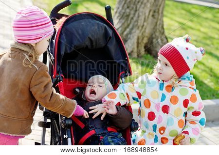 two toddler girls and baby boy on the walk