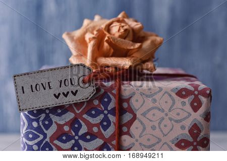 closeup of a gift topped with an artificial flower and with a paper label with the text I love you tied to it with a red string