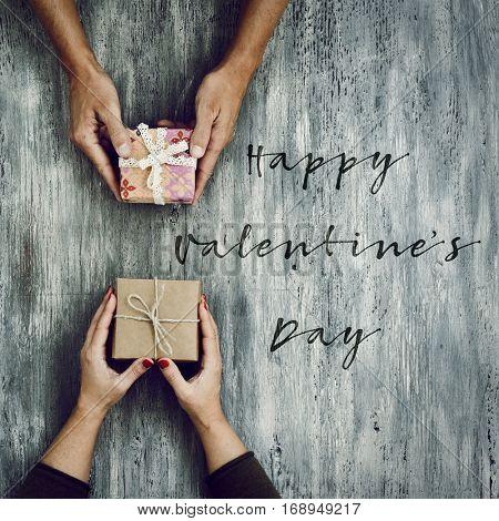 high-angle shot of a young caucasian woman and a young caucasian man exchanging gifts and the text happy valentines day on a rustic wooden table