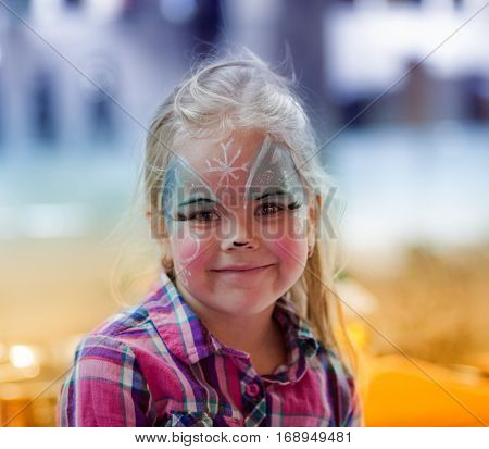 Portrait of beautiful blond little girl with painted face