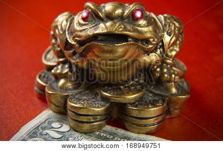 Money frog with ruby eyes and two dollars.