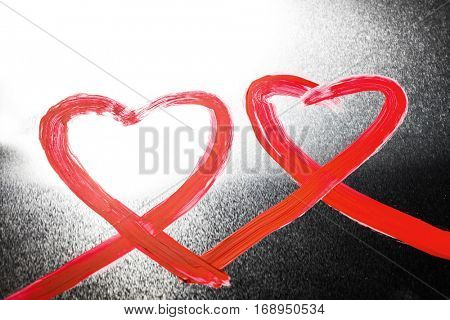 Two abstract red painted hearts on metal background