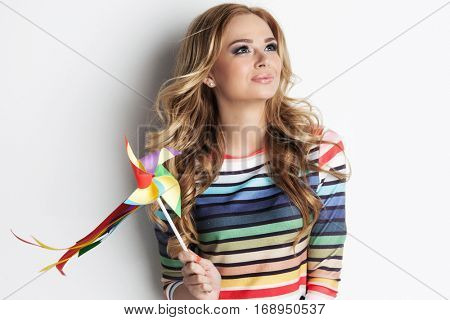 Portrait of beautiful dreamy girl with colorful pinwheel