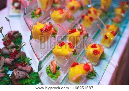Beautifully luxury decorated catering banquet table with black and red caviar and different food snacks on a corporate christmas birthday party event or wedding celebration