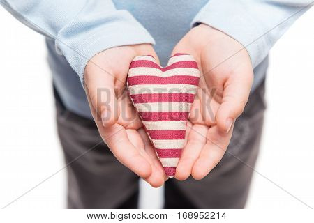 Striped heart in hands of little kid. Isolated on a white background