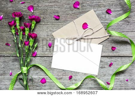blank white greeting card with purple carnation flowers and envelope with green ribbon on rustic wooden background. top view. mock up