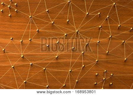 Linking entities. Large network. Network, networking, social media, internet communication abstract. Many small network connected to a larger network. Web of gold wires on rustic wood.