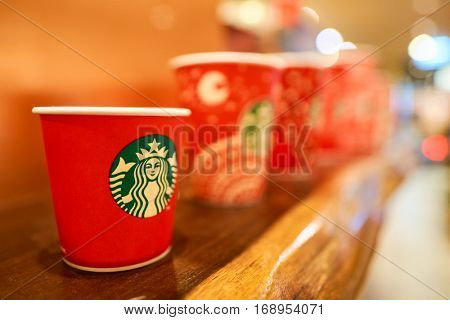 HONG KONG - CIRCA NOVEMBER, 2016: holiday cups at a Starbucks cafe in Hong Kong. Starbucks Corporation is an American coffee company and coffeehouse chain.