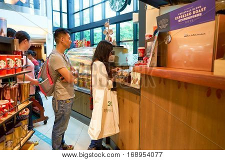 HONG KONG - CIRCA NOVEMBER, 2016: people at a Starbucks cafe in Hong Kong. Starbucks Corporation is an American coffee company and coffeehouse chain.