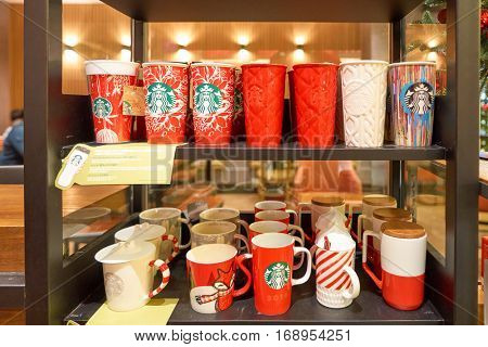HONG KONG - CIRCA NOVEMBER, 2016: red cups on shelves at a Starbucks cafe in Hong Kong. Starbucks Corporation is an American coffee company and coffeehouse chain.