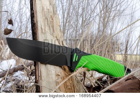 Survival knife on the stump. Survival knife with a black blade and a green handle.