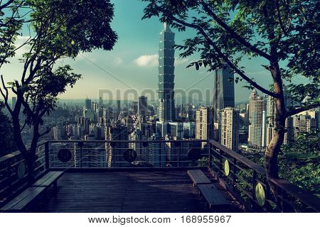 Taipei - December 2016: Viewing deck surrounded by trees and city view with Taipei 101 supertall skyscraper in background.