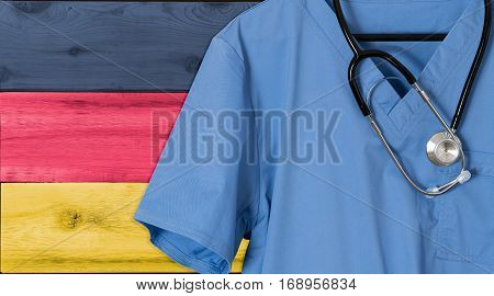 Blue doctor scrubs shirt and stethoscope hang empty in front of German flag. Illustration of medical staff coming from other countries to staff health systems